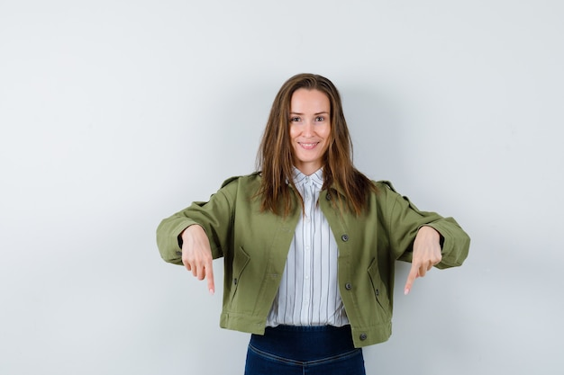 Jeune femme pointant vers le bas en chemise, veste et à la gaieté, vue de face.