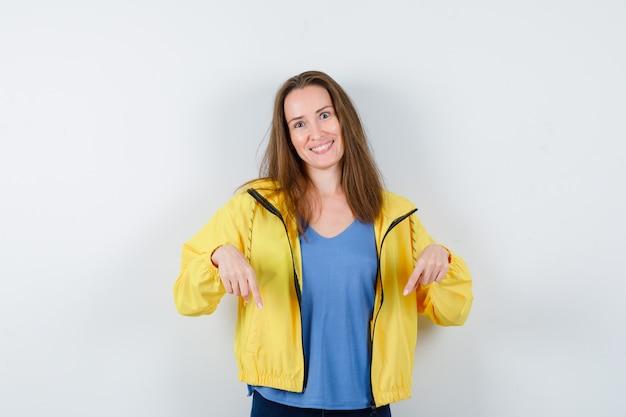 Jeune femme pointant vers le bas en t-shirt et à l'espoir, vue de face.