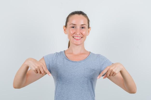Jeune femme pointant vers le bas en t-shirt gris et à la joyeuse, vue de face.