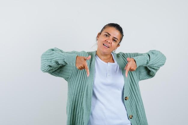 Jeune femme pointant vers le bas en t-shirt, veste et à l'air confiant