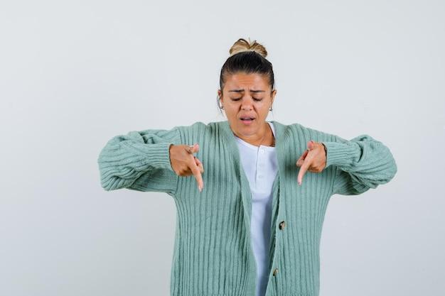 Jeune femme pointant vers le bas en t-shirt, veste et à la stupéfaction