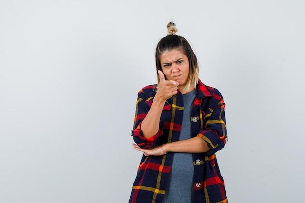 Jeune femme pointant vers la caméra en chemise à carreaux décontractée et l'air lugubre, vue de face.
