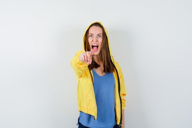 Jeune femme pointant vers la caméra en criant en t-shirt, en veste et en ayant l'air en colère. vue de face.
