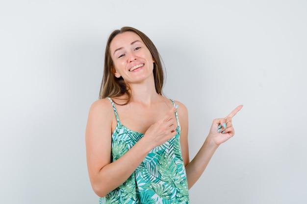 Jeune femme pointant vers le coin supérieur droit en blouse et regardant positive, vue de face.