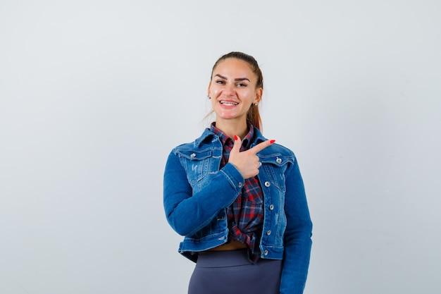 Jeune femme pointant vers le coin supérieur droit en chemise à carreaux, veste, pantalon et l'air heureux. vue de face.