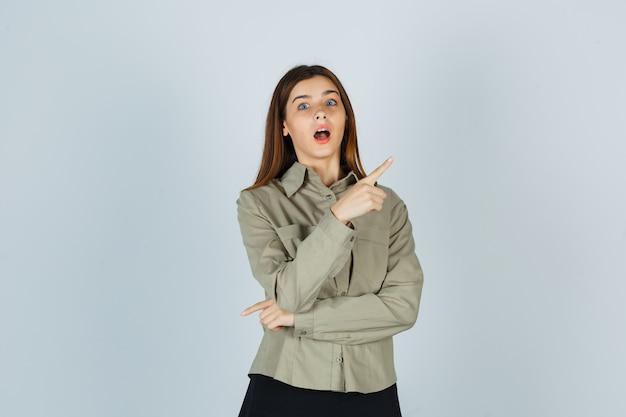 Jeune femme pointant vers le coin supérieur droit en chemise, jupe et se demandant , vue de face.