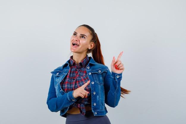 Jeune femme pointant vers le coin supérieur droit en chemise, veste et l'air heureux, vue de face.