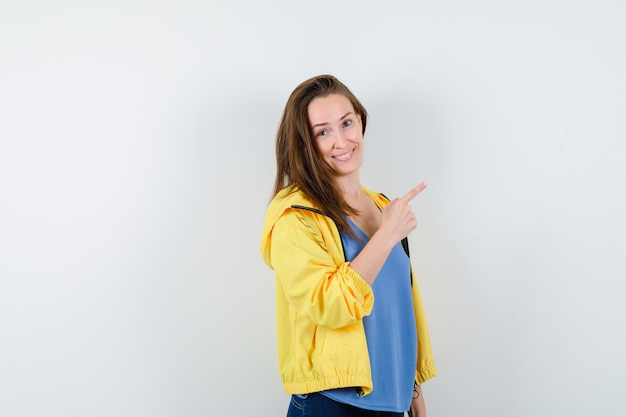 Jeune femme pointant vers le coin supérieur droit en t-shirt, veste et regardant jolly, vue de face.