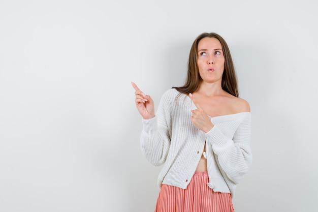 Jeune femme pointant vers le coin supérieur gauche en cardigan et jupe à hésitant isolé