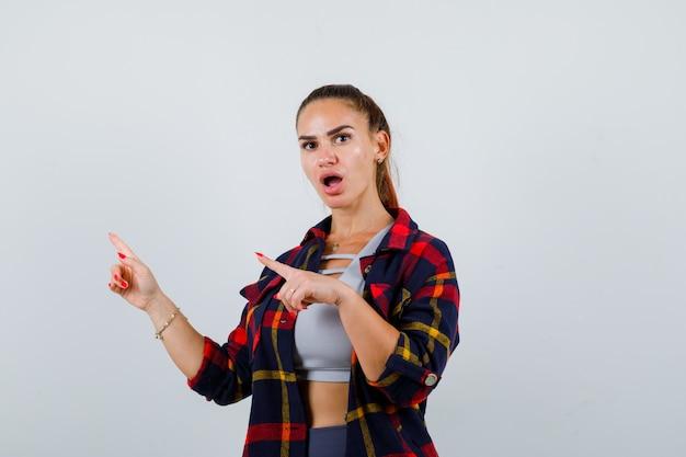 Jeune femme pointant vers le coin supérieur gauche en haut, chemise à carreaux et l'air perplexe, vue de face.