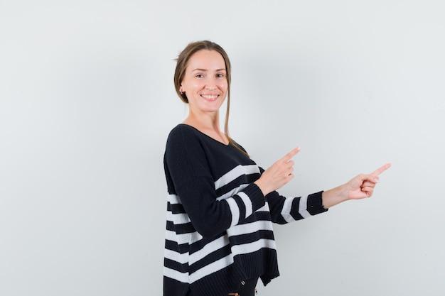 Jeune femme pointant vers le côté en chemise et à l'optimiste