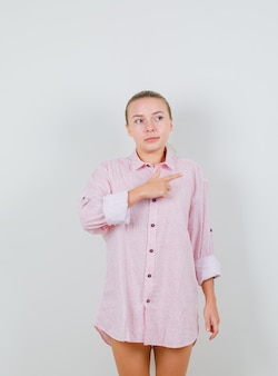 Jeune femme pointant vers le côté en chemise rose et à la curiosité