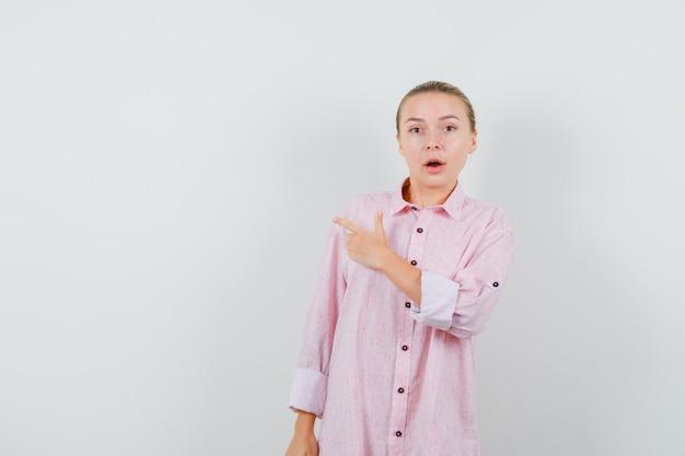 Jeune femme pointant vers le côté en chemise rose et à la surprise