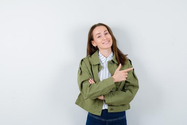 Jeune femme pointant vers le côté droit en chemise, veste et l'air confiant, vue de face.