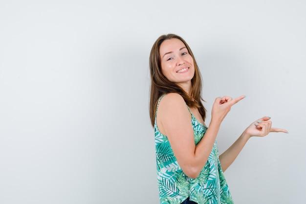 Jeune femme pointant vers le côté droit en chemisier et ayant l'air heureuse. vue de face.