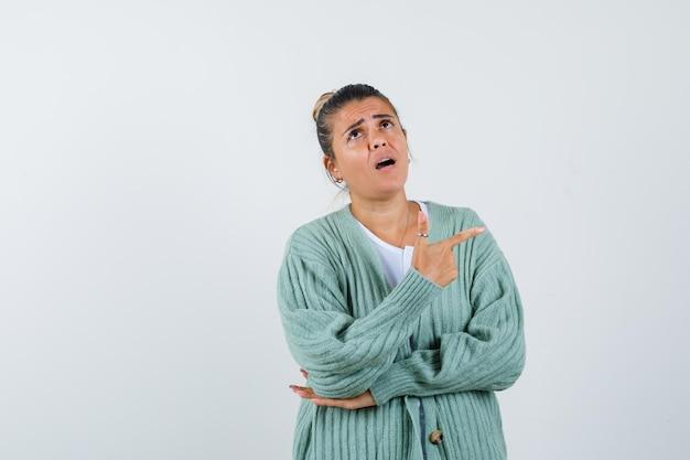 Jeune femme pointant vers le côté droit en t-shirt, veste et semblant étonnée