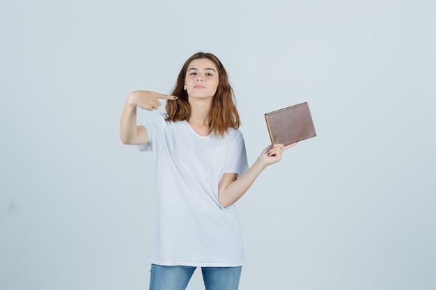 Jeune femme pointant vers le côté droit tout en tenant le livre en t-shirt, jeans et à la confiance. vue de face.
