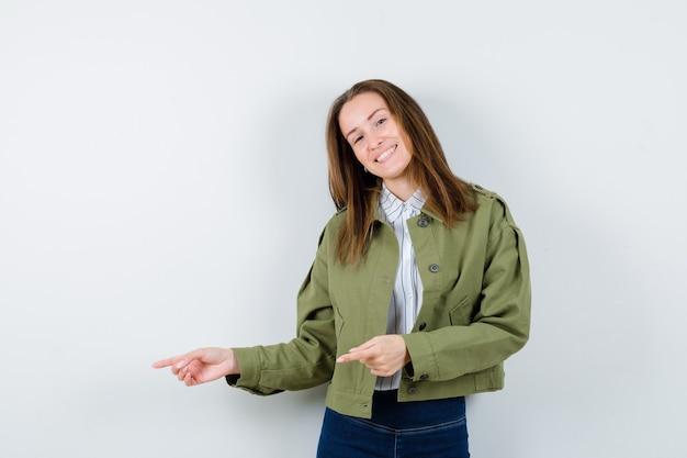 Jeune femme pointant vers le côté gauche en chemise et ayant l'air heureuse. vue de face.