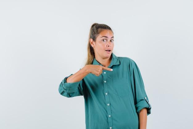 Jeune femme pointant vers le côté gauche en chemise bleue et à la curiosité