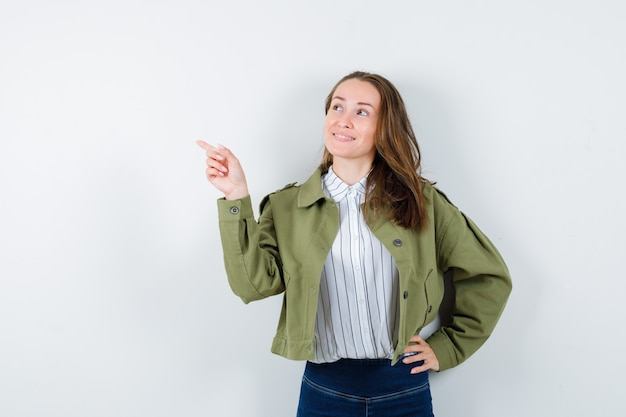 Jeune femme pointant vers le côté gauche en chemise, veste et l'air confiant, vue de face.