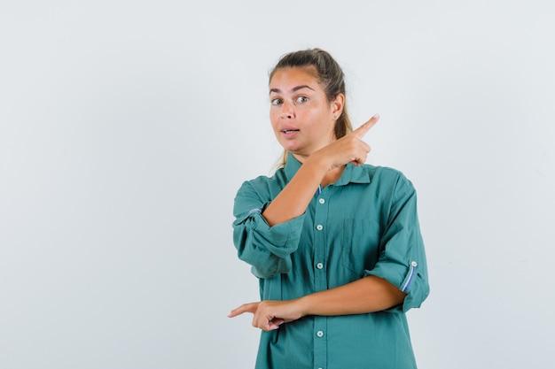 Jeune femme pointant vers des directions différentes avec l'index en chemisier vert et à la recherche attrayante