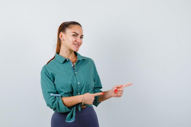 Jeune femme pointant vers la droite en chemise verte et semblant joyeuse. vue de face.