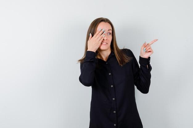 Jeune femme pointant vers la droite et couvrant les yeux