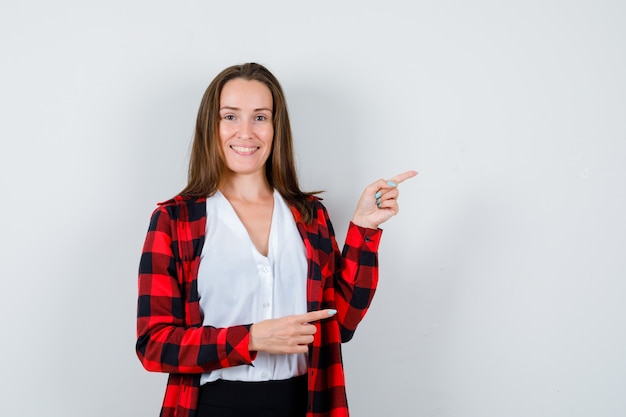 Jeune femme pointant vers la droite dans des vêtements décontractés et semblant joyeuse. vue de face.