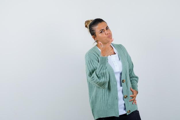 Jeune femme pointant vers la droite avec l'index, tenant la main sur la taille en chemise blanche et cardigan vert menthe et l'air heureux