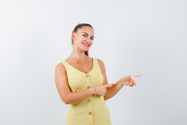 Jeune femme pointant vers la droite en robe jaune et à la joie