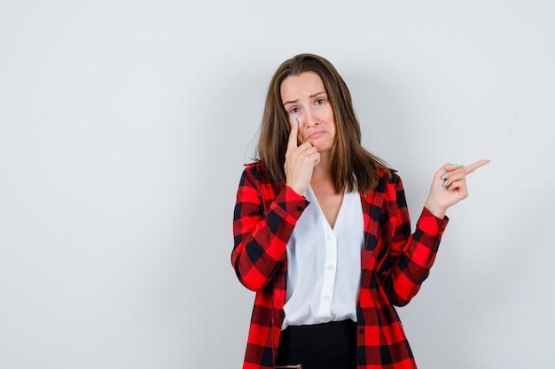 Jeune femme pointant vers la droite et sa paupière dans des vêtements décontractés et l'air triste, vue de face.