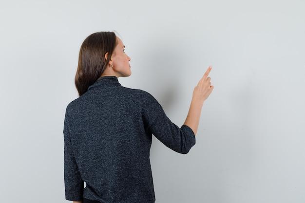 Jeune femme pointant vers l'extérieur en chemise et à la pensive, vue arrière