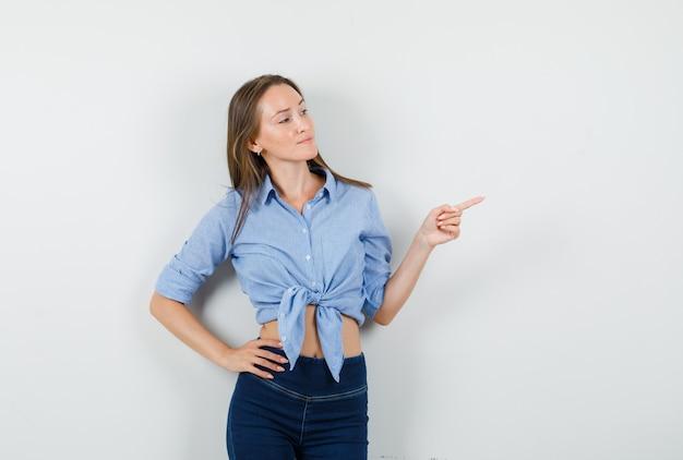 Jeune femme pointant vers l'extérieur avec la main sur la taille en chemise bleue, pantalon et à la confiance