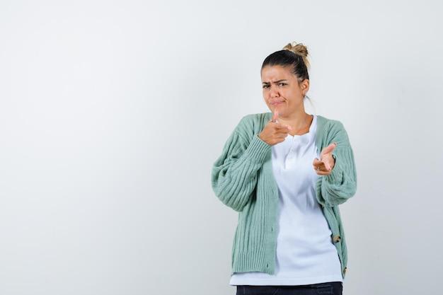 Jeune femme pointant vers l'extérieur en t-shirt, veste et à l'air confiant