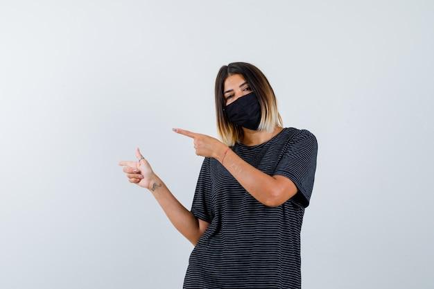 Jeune femme pointant vers la gauche avec l'index en robe noire, masque noir et à la vue de face, heureux.
