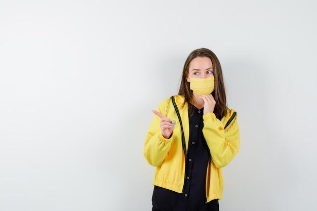 Jeune femme pointant vers la gauche avec l'index