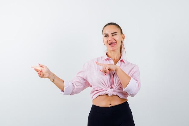 Jeune femme pointant vers la gauche, qui sort la langue en chemise, pantalon et à l'air heureux. vue de face.
