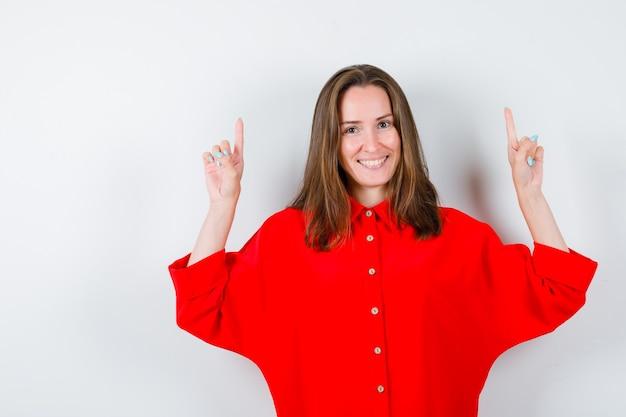 Jeune femme pointant vers le haut en blouse rouge et semblant joyeuse, vue de face.