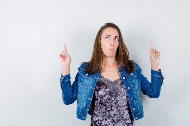 Jeune femme pointant vers le haut en blouse, veste en jean et à la réflexion, vue de face.