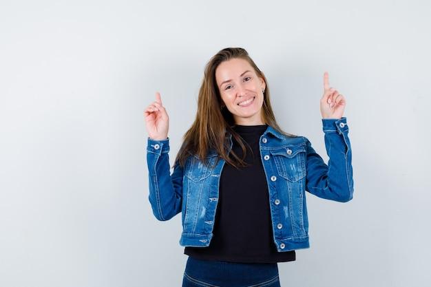 Jeune femme pointant vers le haut en blouse, veste et semblant joyeuse. vue de face.