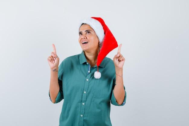 Jeune femme pointant vers le haut en chemise, bonnet de noel et regardant joyeux, vue de face.