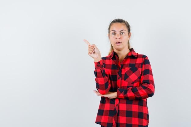 Jeune femme pointant vers le haut en chemise à carreaux et à la perplexité