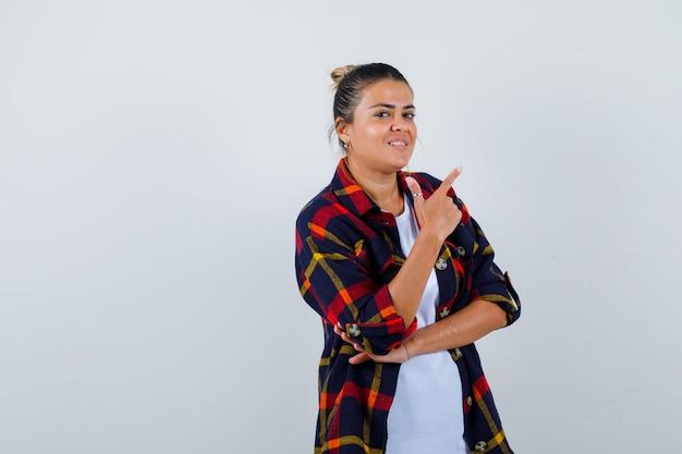 Jeune femme pointant vers le haut en chemise à carreaux et à la réflexion