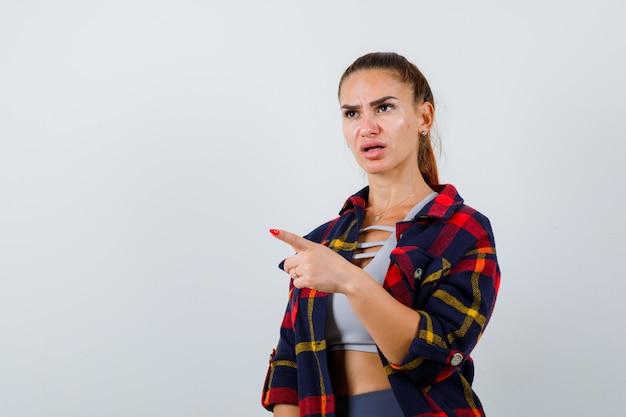 Jeune femme pointant vers le haut, chemise à carreaux et semblant concentrée. vue de face.