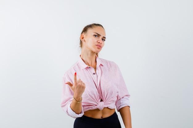 Jeune femme pointant vers le haut en chemise décontractée, pantalon et à la confiance