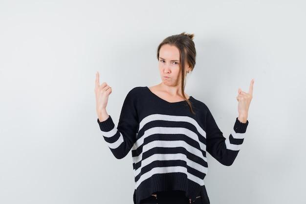 Jeune femme pointant vers le haut en chemise décontractée et à la recherche d'hésitant