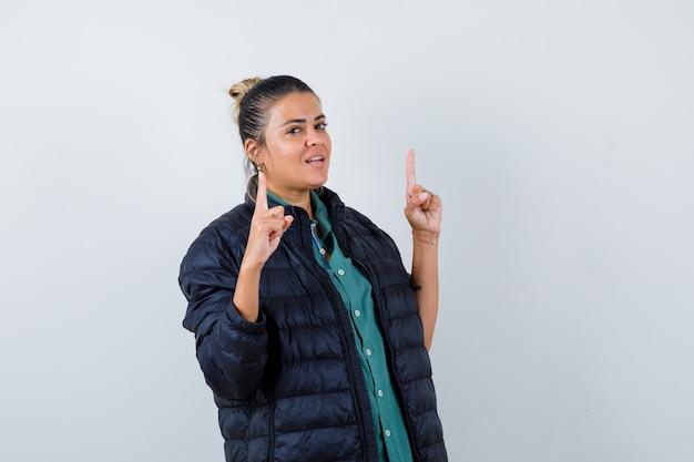 Jeune femme pointant vers le haut en chemise, doudoune et à l'air confiant, vue de face.