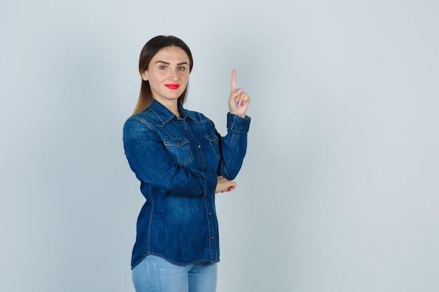 Jeune femme pointant vers le haut en chemise en jean et jeans et à la recherche de plaisir