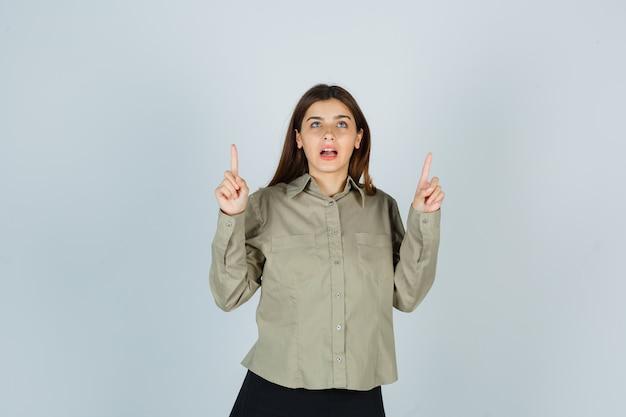 Jeune femme pointant vers le haut en chemise, jupe et à la reconnaissance