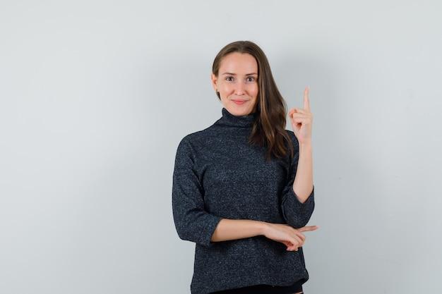 Jeune femme pointant vers le haut en chemise et à l'optimiste